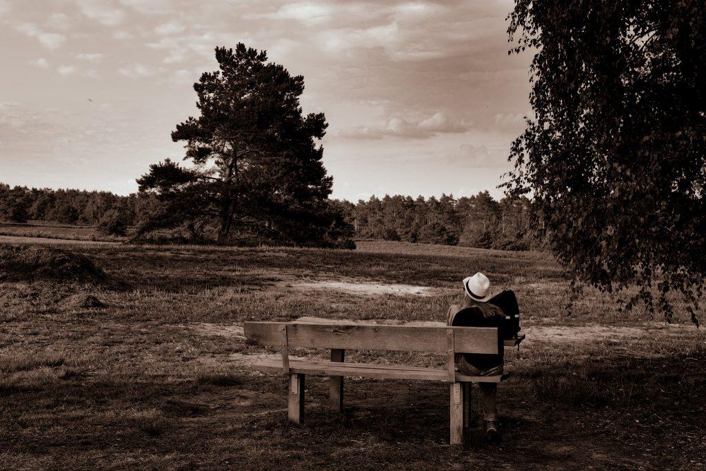 Frau auf einer Bank in der Heide